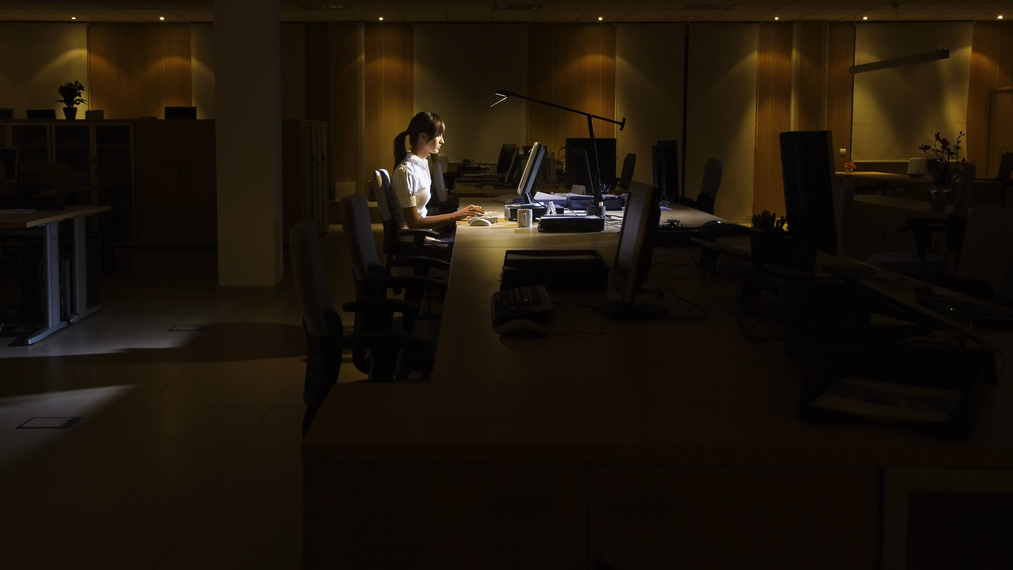 Woman Using Computer In Dark Office