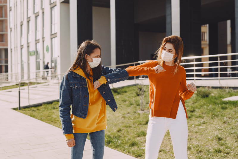 COVID Young women in medical masks greeting each other on city street