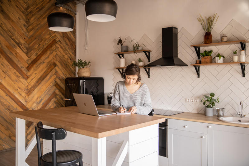 Canva - Busy female freelancer with laptop taking notes in kitchen