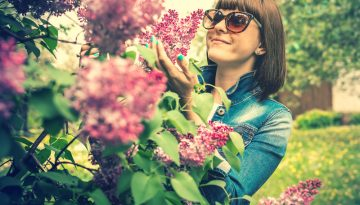 LIlacsCanva - Photo of a woman wearing sunglasses holding lilac flowers
