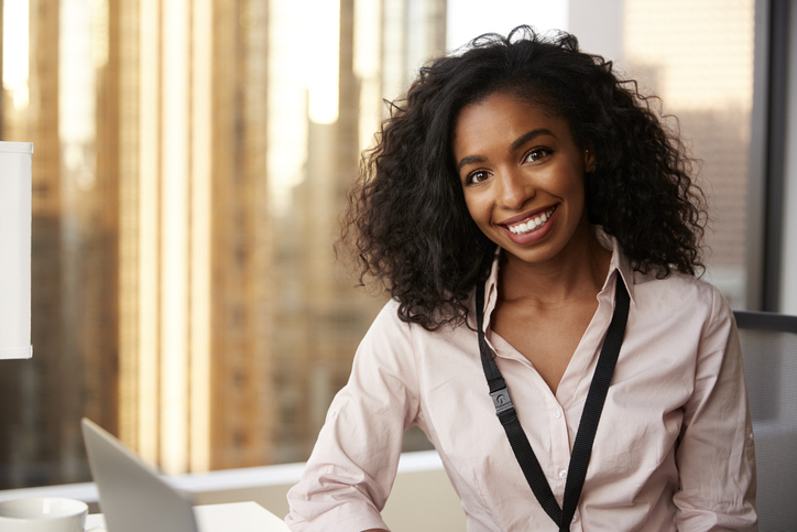 Portrait Of Smiling Businesswoman With Security Pass On Lanyard In Office