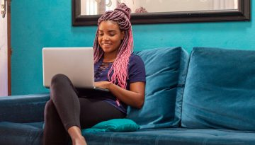 Young black woman with braid using notebook in home room