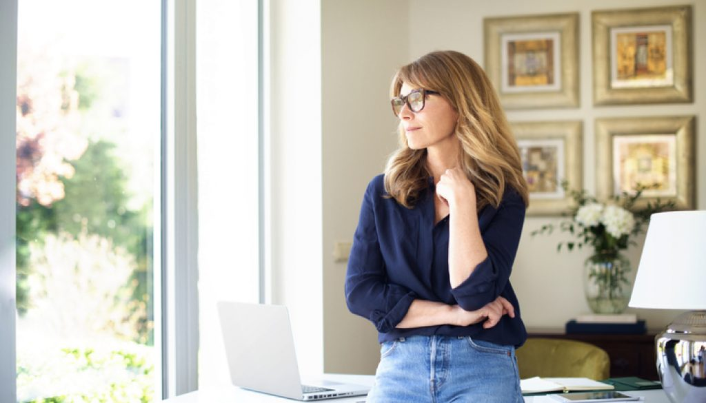 Attractive smiling mature woman standing at desk and thinking