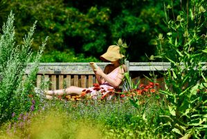 A young lady reading in a botanical garden.