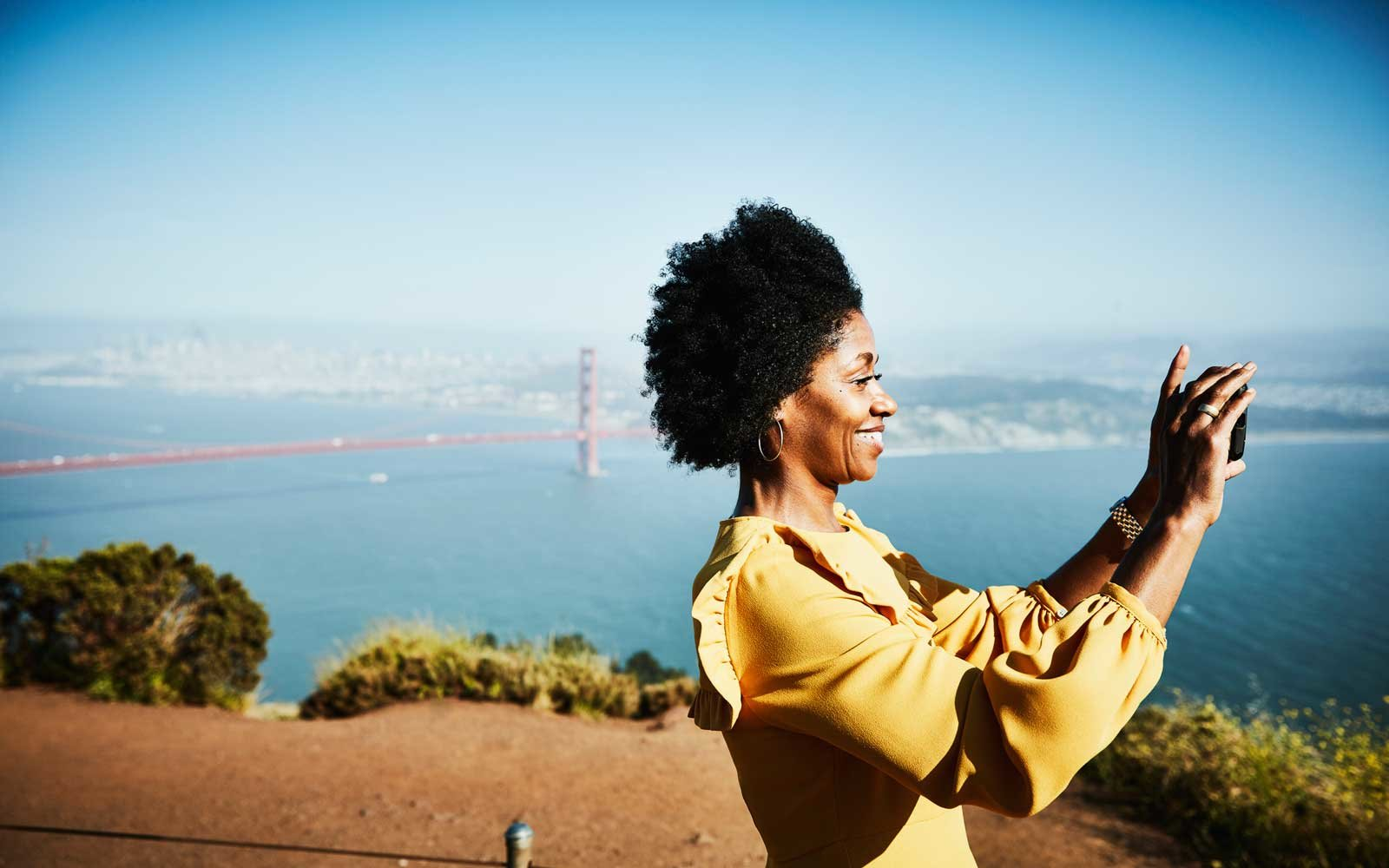 Smiling woman taking photo with smartphone while standing at vista above San Francisco